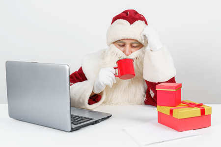 Christmas and New Years concept. Santa Claus is sitting at his desk, drinking coffee and working at the computer. There are Christmas gifts on the table. Stock Photo