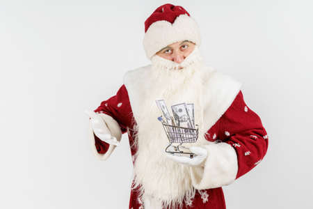 Holidays and Christmas concepts. Santa Claus holds a cart with money on his hand. Isolated on white