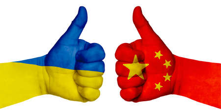 Politics and finance concept. Two hands with a raised finger. They portray the gesture class, managed to negotiate. On the hands of the image of the flags of countries, China and Ukraine