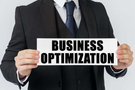 Business and finance concept. A businessman holds a sign in his hands which says - BUSINESS OPTIMIZATION Imagens