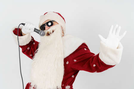 Holidays and christmas concept. Santa Claus sings with a microphone in his hand. Isolated on white