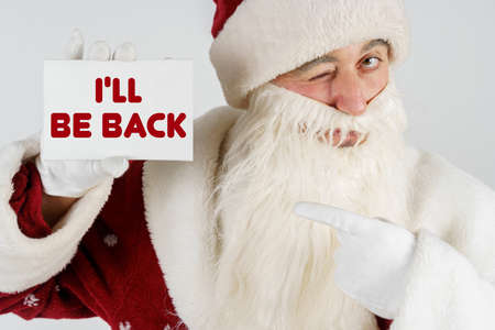 New Year and Christmas concept. Santa Claus holds a card with the text in his hands - I LL BE BACK Stock fotó