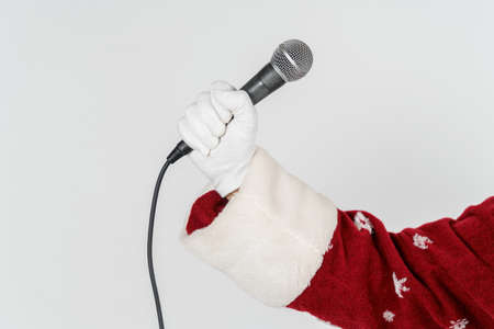 Holidays and Christmas concept. The hand of Santa Claus is holding a microphone in his hand. Isolated on white