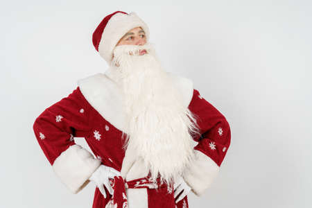 New Year and Christmas concept. Portrait of Santa Claus, holds his hands at the waist, looks to the side.