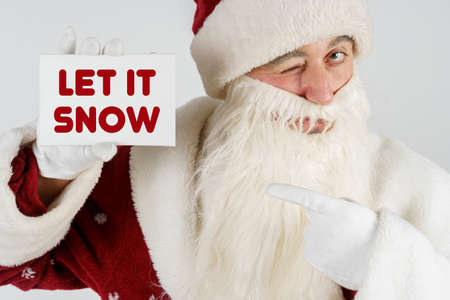 New Year and Christmas concept. Santa Claus holds a card with the text in his hands - LET IT SNOW