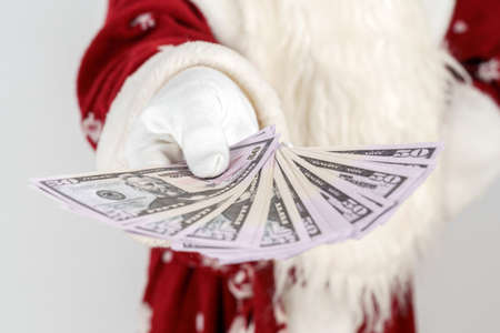 New Year and Christmas concept. Santa Claus holds money in his hands. Isolated on light background