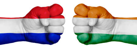 The concept of the struggle of peoples. Two hands are clenched into fists and are located opposite each other. Hands painted in the colors of the flags of the countries. France vs Ireland
