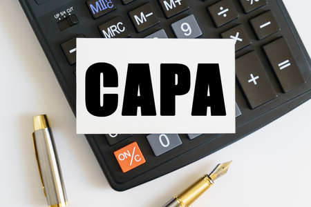 Business and finance concept. On the table there is a pen, a calculator and a business card on which the text is written CAPA. CORRECTIVE AND PREVENTIVE ACTION