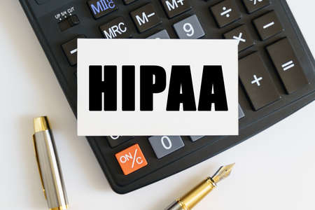 Business and finance concept. On the table there is a pen, a calculator and a business card on which the text is written HIPAA. THE HEALTH INSURANCE PORTABILITY AND ACCOUNTABILITY ACT OF 1996