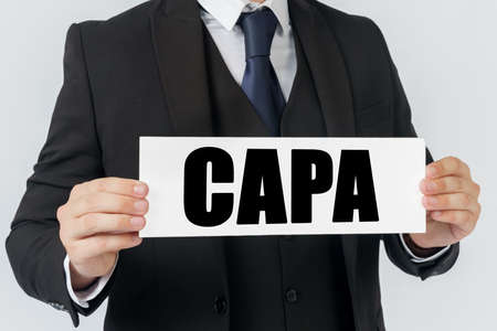 Business and finance concept. A businessman holds a sign in his hands which says CAPA