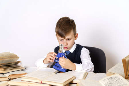 Education concept. The student does homework, studies the microscope. There are many open books on the table.