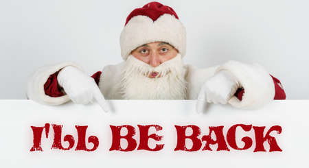 New Year and Christmas concept. Santa Claus points his fingers at the board with the text - I LL BE BACK