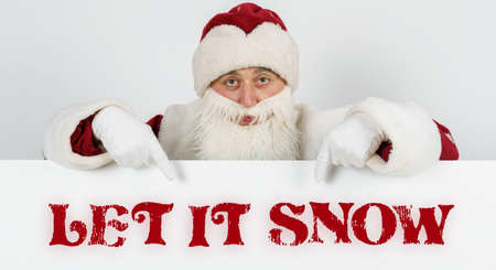 New Year and Christmas concept. Santa Claus points his fingers at the board with the text - LET IT SNOW Stock Photo