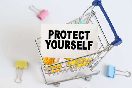Business concept. In the shopping cart, the text is written on the card - PROTECT YOURSELF.