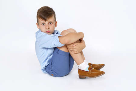 Education concept. The child is a boy sitting on the floor with his arms around his legs. Isolated on white background. 写真素材