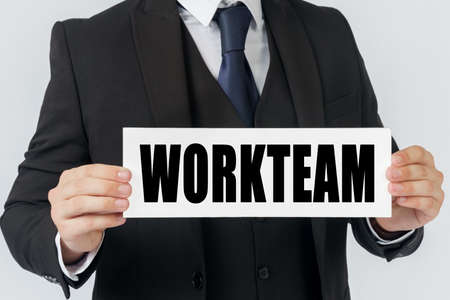 Business and finance concept. A businessman holds a sign in his hands which says WORKTEAM