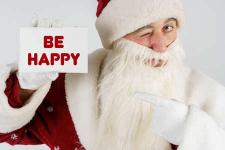 New Year and Christmas concept. Santa Claus holds a card with the text in his hands - BE HAPPY