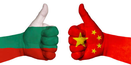 Politics and finance concept. Two hands with a raised finger. They portray the gesture class, managed to negotiate. On the hands of the image of the flags of countries, China and Bulgaria