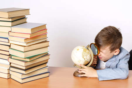 Education concept. The student does homework, studies the globe. He has books on both sides.