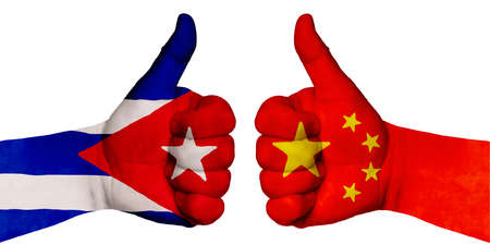 Politics and finance concept. Two hands with a raised finger. They portray the gesture class, managed to negotiate. On the hands of the image of the flags of countries, China and Cuba