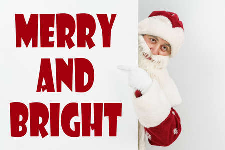 New Year and Christmas concept. Santa Claus points his fingers at the board with the text - MERRY AND BRIGHT
