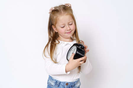 Children concept. A girl holds an alarm clock in her hands, plays with it. Isolated over white background.