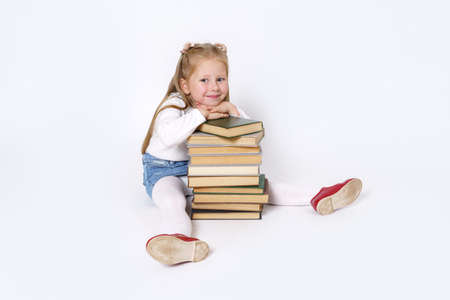 Education and people concept. Portrait of a child girl who sits near the books and looks at the camera. Isolated on white background.
