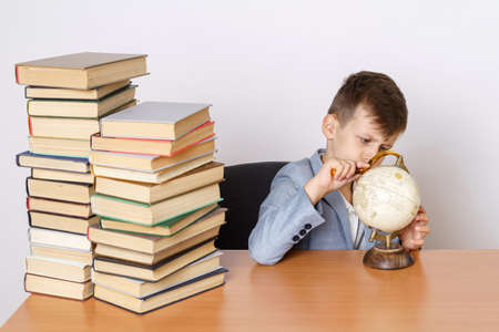Education concept. The student does homework, studies the globe. He has books on both sides. Stok Fotoğraf