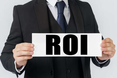 Business and finance concept. A businessman holds a sign in his hands which says ROI - RETURN ON INVESTMENT Imagens