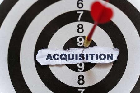 Business and finance concept. A piece of paper with the text is nailed to the target with a dart - ACQUISITION Zdjęcie Seryjne