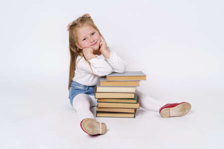 Education and people concept. Portrait of a teenage girl who sits near the books, leaning on them. Isolated over white background.