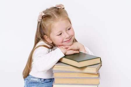 Education and people concept. Portrait of a child girl who sits near the books and rested her head on the books. Isolated on white background. Banque d'images