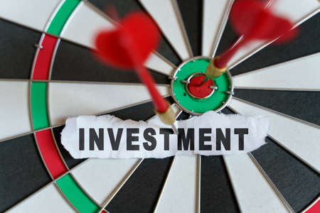 Business and finance concept. A piece of paper with the text is nailed to the target with a dart - INVESTMENT 免版税图像