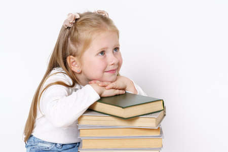 Education and people concept. Portrait of a child girl who sits near the books and rested her head on the books. Isolated on white background.