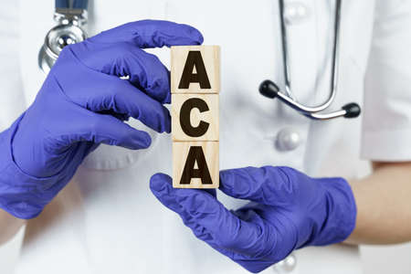 Medicine and health concept. The doctor holds cubes in his hands on which it is written - ACA. AFFORDABLE CARE ACT.