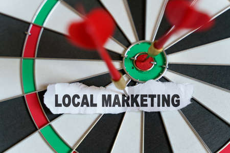 Business and finance concept. A piece of paper with the text is nailed to the target with a dart - LOCAL MARKETING