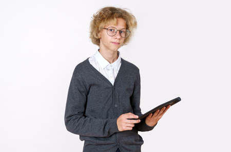 Education concept. Boy teenager uses a tablet. Isolated over white background.