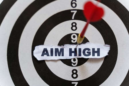 Business and finance concept. A piece of paper with the text is nailed to the target with a dart - AIM HIGH