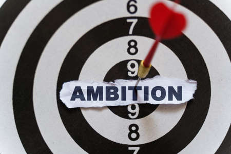 Business and finance concept. A piece of paper with the text is nailed to the target with a dart - AMBITION