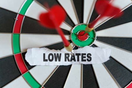 Business and finance concept. A piece of paper with the text is nailed to the target with a dart - LOW RATES