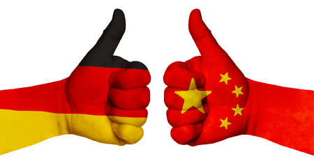 Politics and finance concept. Two hands with a raised finger. They portray the gesture class, managed to negotiate. On the hands of the image of the flags of countries, China and Germany