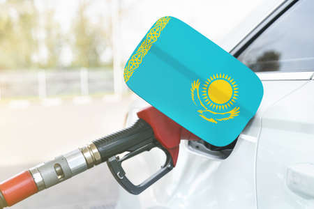 Energy and economy concept. Flag of Kazakhstan on the car's fuel filler flap with gas pump nozzle in the tank.
