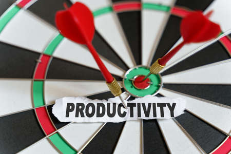 Business and finance concept. A piece of paper with the text is nailed to the target with a dart - PRODUCTIVITY