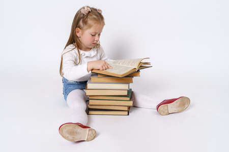 Education and people concept. Portrait of a teenage girl who sits near books and reads. Isolated over white background.