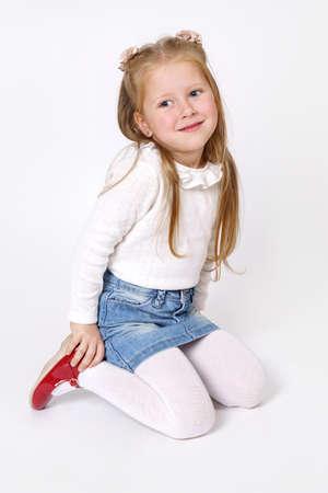 Children concept. The girl is sitting on the floor. Isolated over white background. Standard-Bild