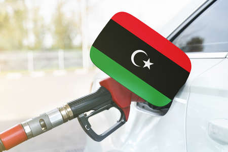 Energy and economy concept. Flag of Libya on the car's fuel filler flap with gas pump nozzle in the tank.