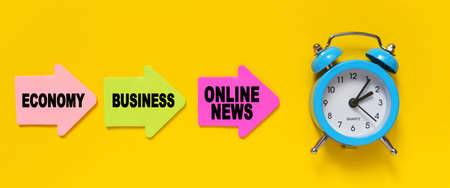 Finance and economics concept. On a yellow background, a blue alarm clock, and paper arrows. On the pink arrow it says - Economy, on the yellow - Business and on the red - ONLINE NEWS