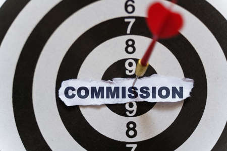 Business and finance concept. A piece of paper with the text is nailed to the target with a dart - COMMISSION