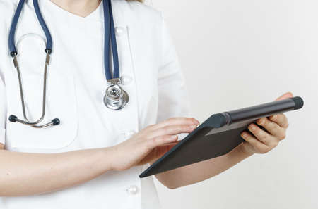Medicine and health concept. The doctor writes the information into the tablet. Isolated on white background.