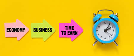 Finance and economics concept. On a yellow background, a blue alarm clock, and paper arrows. On the pink arrow it says - Economy, on the yellow - Business and on the red - TIME TO EARN